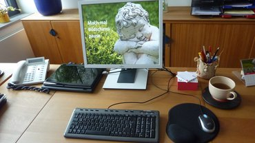 Schreibtisch mit Bildschirm, aif dem eine kleine steinerne Putte zu sehen ist, die sich ausruht