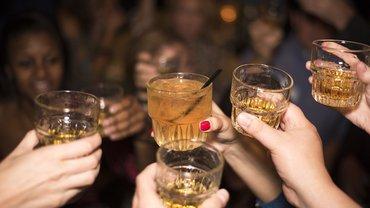 mehrere Händer stoßen mit Whiskeygläsern an, im Hintergrund verschwommene Gesichter